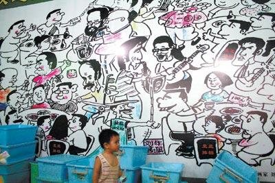 吉慶街藝人來自五湖四海,有店家在大型白板上畫了這幅漫畫,這小孩說,他長大後也要做街頭藝人賣藝。李安君/攝影