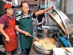 ▲擁有微電腦溫控烤餅機的天津勝記餅店,由王勝利(左)與丈夫古珍朋攜手做出北方味。攝影  高政全