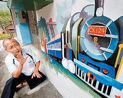▲鐵道畫家李明建坐在自繪的壁畫前解釋他為什麼熱愛畫鐵道。攝影  陳信翰
