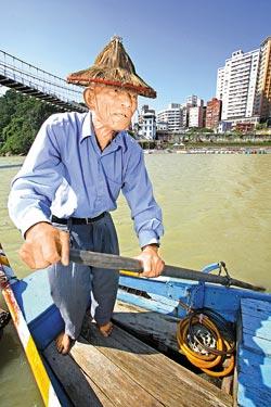 ▲81歲的施朱有努力在畫舫上搖槳,他說這是生活的重心與樂趣。攝影  黃國書