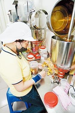 ▲魏記麥芽餅是以手工方式,一個一個將麥芽糖夾在鹹酥餅乾中間。攝影  楊為仁